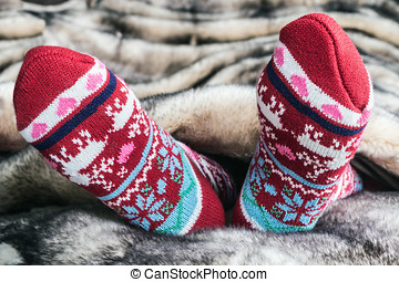 Female legs in Christmas socks under a blanket of fur