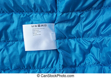 Label with washing instructions, on blue fabric background