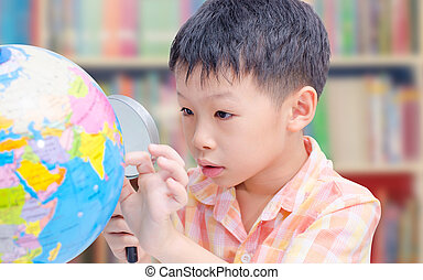 Asian boy looking at a globe in library