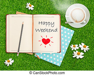 Happy Weekend on notebook with coffee cup on grass field.