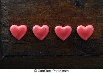 Four red heart on wooden background for valentines day or...