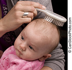 Mother combing baby hair - Mother brushing her daughter s...