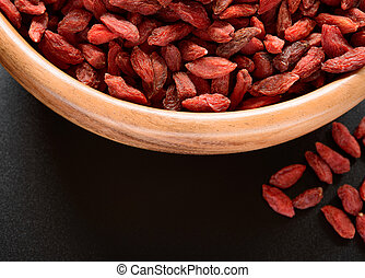 Wooden Bowl Full of Dried Goji Berries on the Black Table...