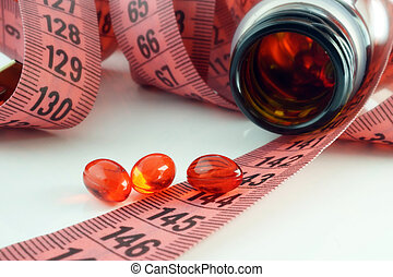 supplements of diet - Measuring tape and bottle with pills....