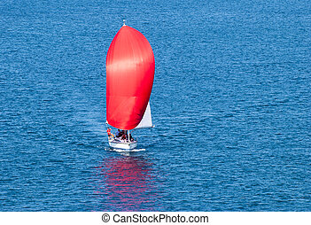 Red Sail - The view of a yacht with a bright red sail in...