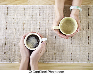 hands holding coffee - two people talking while drinking...