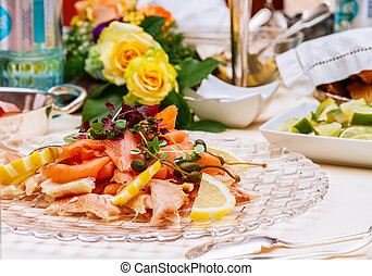 smoked fish platter served with fresh lettuce and garnished...
