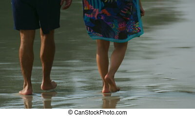 Beach walking - Couple walking barefoot on wet sand Similan...
