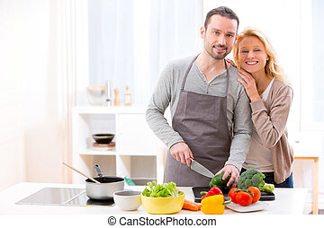 Young attractive couple cooking in a kitchen - View of a...