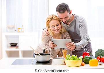 Young attractive couple reading recipe on a tablet - View of...