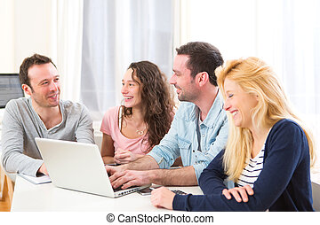 Group of 4 young attractive people working on a laptop