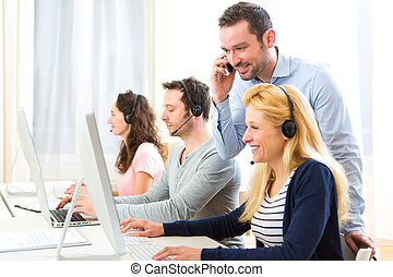 Manager training a young attractive people on computer -...