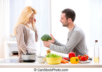 Young attractive couple having fun in the kitchen - View of...