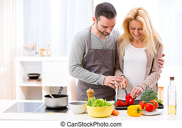 Young attractive man helping out his wife while cooking -...