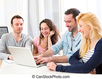 Group of 4 young attractive people working on a laptop -...