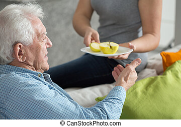 Fruit for dessert - Elderly man eating fruit for dessert