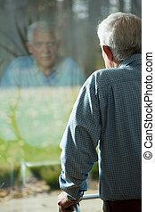 Looking through the window - Elderly weak man looking...