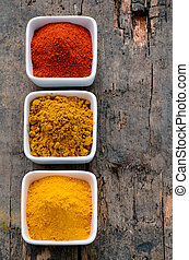Hot red chili powder, curry and turmeric powder on wooden...