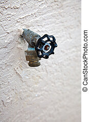 water spigot with backflow preventer valve on stucco wall
