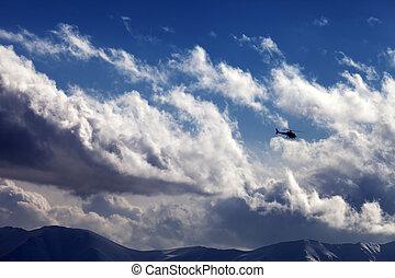 Helicopter in cloudy sky. Ski resort Gudauri. Caucasus...