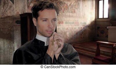 catholic priest saying a prayer - portrait of clergyman...