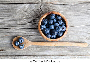 Blueberries on a wooden bowl, spoon on wooden background