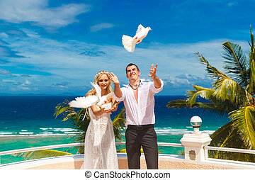 The happy bride and groom with white doves on a tropical...