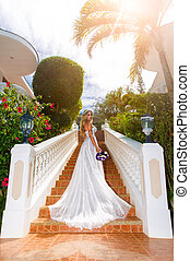 Beautiful bride in wedding dress with long train standing on...