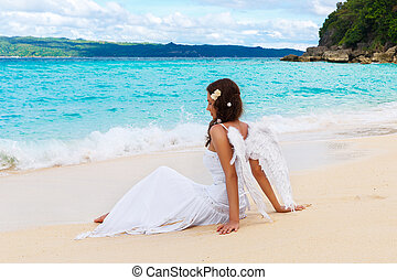 Beautiful young bride with angel wings on the sea coast....