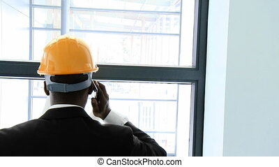 Afro-American architect on phone studying a building