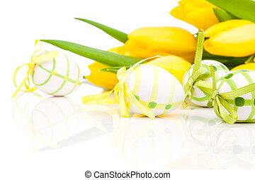 easter eggs with yellow tulip flowers isolated on white backgrou
