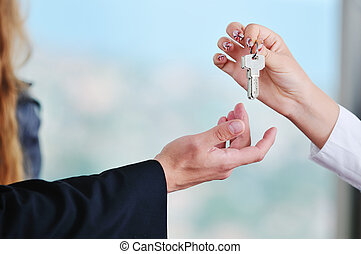 new home keys - man and woman hand closeup with home keys...