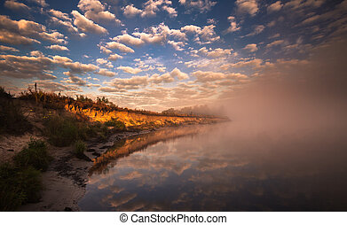 misty morning on the river and clouds reflected in water -...