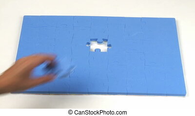 Person placing the last piece on a puzzle