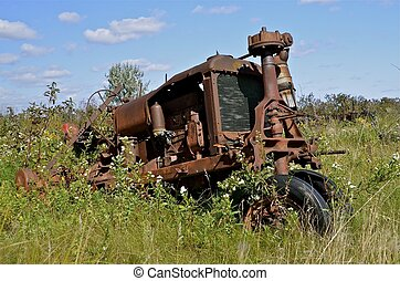 Antique tracter in junkyard - A very old tractor is parked...