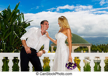 Happy bride and groom standing next to the stone gazebo amid...