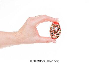 easter egg - female hand holding a easter egg against white...