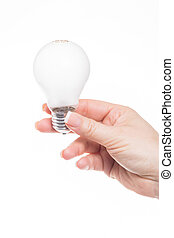 energy saving - female hand holding al ight bulb against...