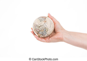 travel round the world - female hand holding a little globe...