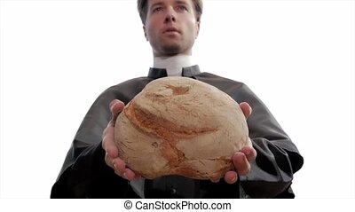 catholic priest breaking bread - clergyman breaks bread as...
