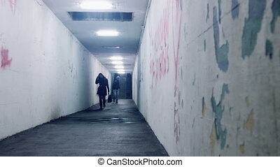 woman robbed from a thief tunnel - woman walking in a...