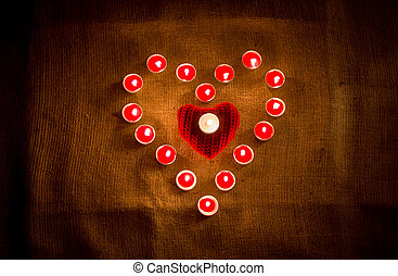 red candles forming heart shape on linen cloth - Decorative...