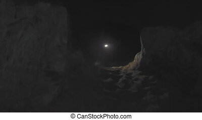 Caver in the cave - man with lantern sneaks into narrow...