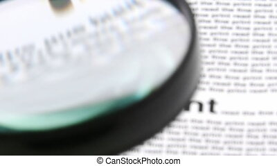 Magnifying glass showing words from a newspaper