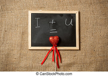 equation of love written on blackboard with red heart -...