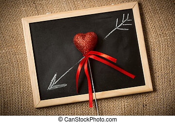 drawn on chalkboard arrow going through decorative heart -...