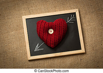photo of knitted heart lying on blackboard with drawn arrow