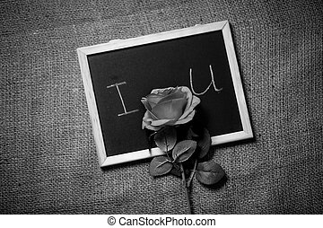 Monochrome photo of declaration of love on blackboard with rose