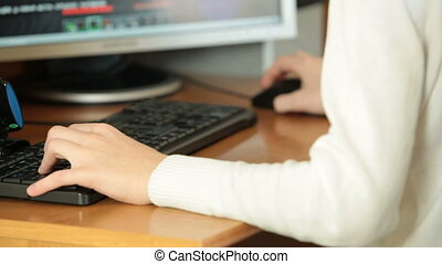 Gamer child's hands on the keyboard playing computer games on desktop pc