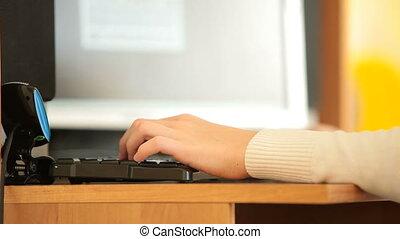 Gamer hand typing on keyboard playing games on desktop...